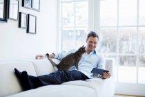 Человек расслабляется на диване с помощью цифрового планшета с кошкой — стоковое фото
