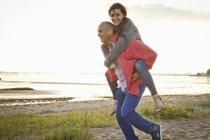 Homme donnant piggyback tour à la femme sur la plage — Photo de stock