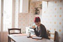Junge Frau sitzt am Tisch Kaffee trinken, Blick in die digital-Tablette — Stockfoto