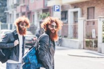 Young male hipster twins with red hair and beards strolling on road — Stock Photo