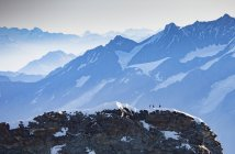 Snowcapped mountains landscape with distant hikers on peak — Stock Photo