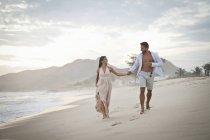 Metà di coppie di adulte camminano lungo la spiaggia, mano nella mano — Foto stock