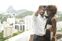 Coppia che prende selfie sulla terrazza, Sugar Loaf Mountain sullo sfondo, RIo, Brasile — Foto stock