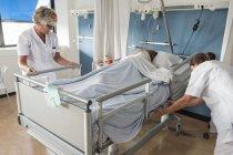 Ärztinnen mit Patientin im Krankenhausbett — Stockfoto