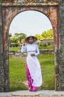 Mid adult woman standing in archway wearing ao dai and conical hat looking at camera, Hue, Vietnam — Stock Photo