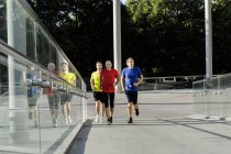 Male runners jogging alongside glass balustrade in city street — Stock Photo