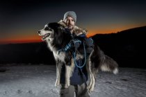 Portrait of mature man carrying dog in snow at night — Stock Photo
