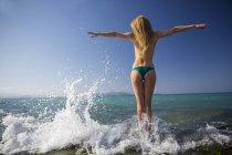 Вид сзади молодой женщины, стоя в море с распростертыми объятиями — стоковое фото