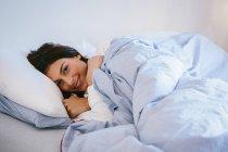 Jeune femme au lit — Photo de stock