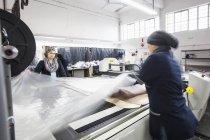 Работницы фабрики разворачивают текстиль на станке для резки узоров на швейной фабрике — стоковое фото