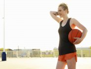 Young female basketball player in training in parking lot — Stock Photo
