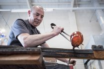 Glassblower forming molten glass — Stock Photo