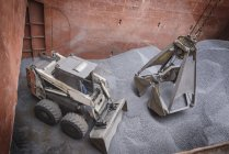 High angle view of digger and grab unloading metal alloy in ships hull — Stock Photo