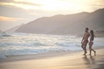 Mid adult couple on beach, wearing swimwear, walking towards ocean — Stock Photo