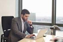 Homem de negócios que trabalha no portátil no interior do escritório — Fotografia de Stock