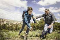 Father and teenage son chasing each other on hiking trip, Cody, Wyoming, USA — Stock Photo