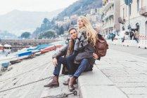 Молода пара, сидячи на березі озера, озера Комо, Італія — стокове фото