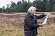 Senior man looking at map — Stock Photo