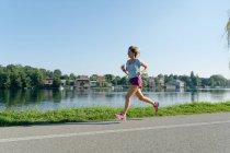 Mulher adulta média correndo na estrada ao lado do lago — Fotografia de Stock