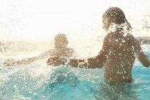 Couple having fun, splashing around in outdoor swimming pool — Stock Photo