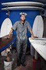 Портрет мужчины среднего возраста и доски для сёрфинга в мастерской — стоковое фото