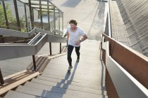 Male runner running up urban stairway — Stock Photo