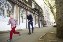 Padre e figlio caucasico che corrono per strada, Londra, Regno Unito — Foto stock