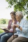 Seniorin und reife Enkelin sitzen auf Parkbank und lesen Bibel — Stockfoto