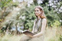 Giovane donna in campo distratta dalla lettura del libro — Foto stock