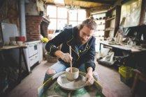 Бородатий середині дорослої людини в майстерні, сидячи на гончарному колі за допомогою diddler зробити глиняний горщик — стокове фото