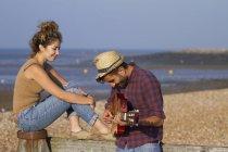 Jovem casal na praia, homem tocando guitarra — Fotografia de Stock