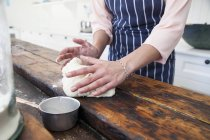 Cropped image of woman shaping dough at kitchen counter — Stock Photo