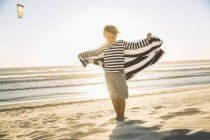 Full length front view of boy on beach wearing striped t-shirt holding towel looking at camera — Stock Photo