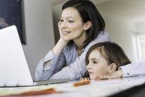 Мать и дочь используют ноутбук дома — стоковое фото