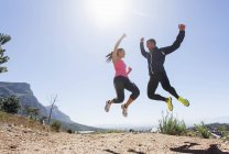 Young joggers jumping in mid air — Stock Photo
