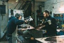 Мужчины-металлисты молотят медь на кузнице — стоковое фото