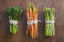 Grappes de carottes, de brocolis et d'asperges liées par des cordes — Photo de stock
