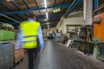Задній вид працівник ходити в гумові цеху, розмиті руху — стокове фото