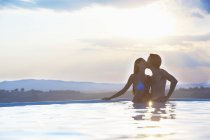 Romantic couple kissing in outdoor swimming pool — Stock Photo
