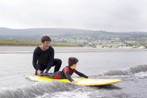 Father teaching son how to surf — Stock Photo