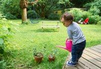 Малюк хлопчик поливу рослин, у дворі — стокове фото