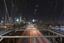 Elevated view of traffic light trails crossing Manhattan Bridge at night, New York, USA — Stock Photo