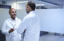 Mature male doctors taking break and talking in office — Stock Photo