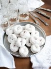 Tray of sugar powdered donuts with glasses of water — Stock Photo