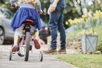 Figlia d'istruzione del padre per guidare la bicicletta su strada — Foto stock