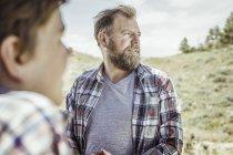 Мужчина и сын-подросток, выглядывающие из пейзажа, Бриджер, Монтана, США — стоковое фото