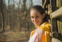 Портрет молодої жінки, притулившись паркан у лісі — стокове фото