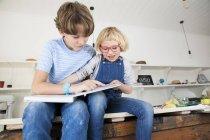 Mädchen greifen Bilderbuch von Bruder auf Küchentisch — Stockfoto