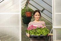 Plantes de tenue de jeune femme — Photo de stock