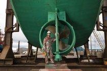 Портрет мужчины корабельного художника перед зелёным корабельным винтом — стоковое фото